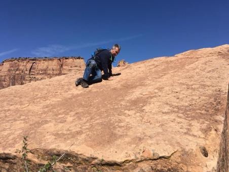 Michael climbing slick rock with engraving of the Declaration of Independence