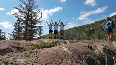 Bonnie, Michael and Mo giving the victory sign on top of a big rock off the trail