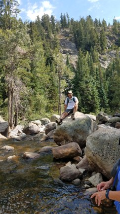 Michael taking a break sitting on a big rock just off the trail