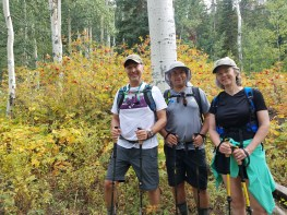 Michael, Mo and Bonnie standing in front of a patch of yellow flowers along the trail