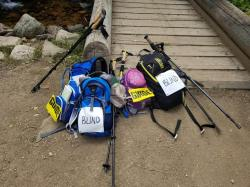 Backpacks and trekking poles stacked at the begining of a wooden bridge