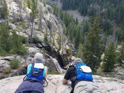 Michael and Bonnie laying on a rock ledge looking down at the bottom of Fish Creek Falls