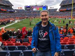Michael wearing his Texans shirt with football field in background