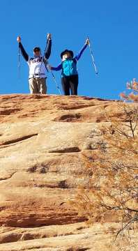 Michael and Linda standing at top of mountain with arms raised in victory sign