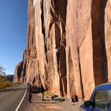 Rock climber scaling cliff near road