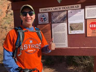 Michael wearing orange Astros shirt in front of Corona Arches Trailhead sign