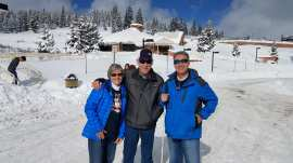 Janice, Bud and Michael standing in rest stop parking lot with two feet of snow in background