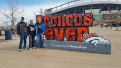 Bud, Janice and Michael in front of Broncos sigh outside the stadium