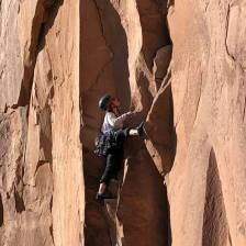 Closeup of rock climber scaling cliff near road
