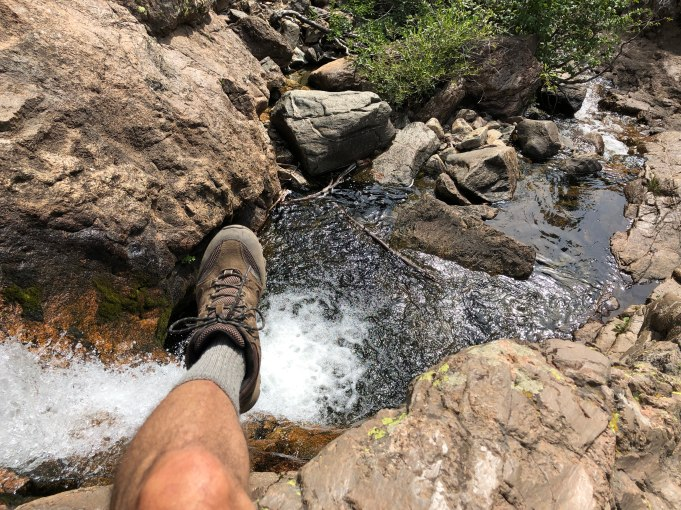 Michael taking a break and hanging his foot over the side of a rock looking down at the creek below