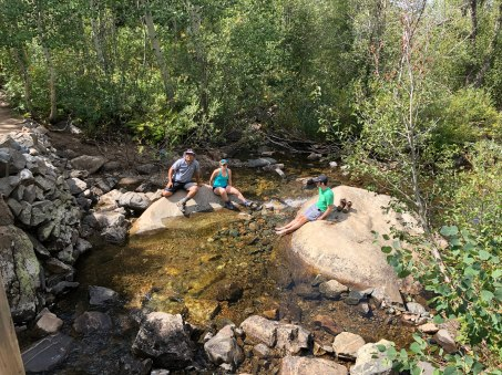 Mo, Bonnie and Zach taking a break on some big rocks in the creek