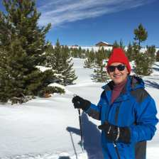 Michael wearing his red ski cap standing on the trail in his skis with trees and red barn in the background
