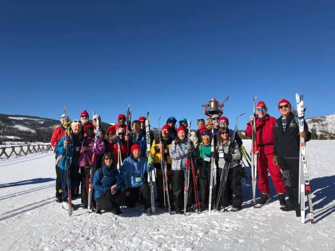 Team Texas with their guides taking their group photo out on the snow under bright blue skies