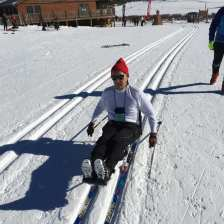 Michael poling along a track in the sit ski