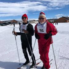 Michael and Einar with skis and number 56 bibs on ready to line for the 5K Rally