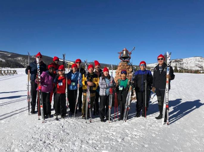 Team Texas holding their skis and poles taking their group photo out on the snow under bright blue skies