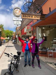 Michael and Janice standing next to tandem bike in front of Brown Cycle shop with arms raised in victory sign at the end of the ride