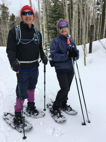 Michael showing off his pink gaiters and Janice standing next to him on the snow