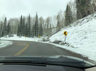 Driving to Grand Mesa with snow packed mountains on both sides of the highway