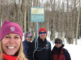 Linda, Janice, Michael and Marlys posing at beginning of the snow covered trail