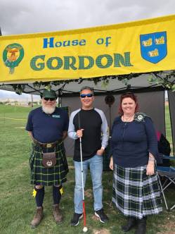 Michael standing in front of Gordon clan tent with two Scots from teh clan