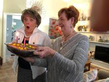 "Fran and Ella holding their birthday cake as everyone sings, ""Happy Birthday to You"""