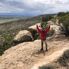 Michael standing at the top of Hawkeye Trail with arms raised in victory sign