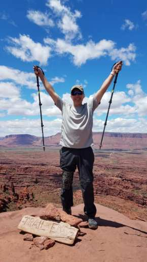 Micheal at the top of Fisher Towers Trail with arms raised in victory sign