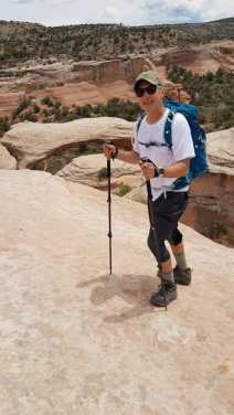 Michael standing on inclined slip rock leading down to the first arch