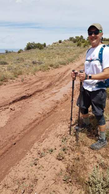 Michael standing bu mudd 4-wheeler tracks on dirt road trail to Rattlesnake Arches