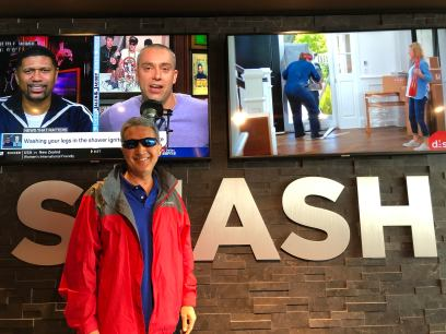 Michael standing in front of Smash Burger sign with two big-screen TVs in the background in Denver Airport