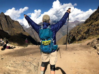 Michael standing at the top of Dead Woman's Pass with arms raised in victory pose